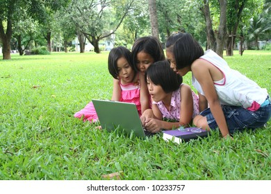 Young girls using computer in the park (series)