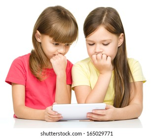 Young girls are using tablet while sitting at table, isolated over white