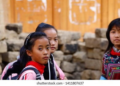Young girls in a village near the rice fields of Yunnan, China. The famous terraced rice fields of Yuanyang in Yunnan province in China. Yunnan, China - November, 2018.