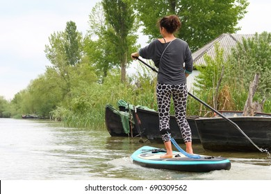 Young girl-surfer riding on the stand-up paddle board SUP in clear waters of the channels of city of Vilkovo in Ukraine on the background of green trees