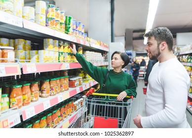 Young glad couple standing near shelves with canned goods at store. Young people with a cart choose canned vegetables in a supermarket. Family shopping at the store.