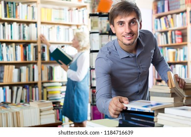 Young glad man choosing new book from many in book shop