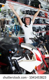 Young glad man sitting on the bike in helmet in the shop