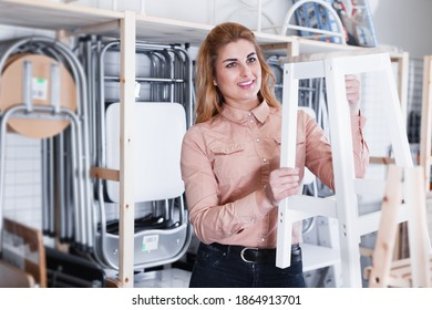 Young glad woman choosing comfortable backless stool in home furnishings store