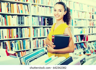 Young glad woman taking books in hard cover in bookstore
