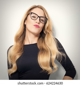 Young glamorous blond businesswoman or secretary posing on a light background.