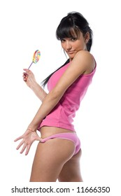 Young glamorous and sexy woman posing in pink underwear with lollipop. Isolated over white background