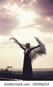 Young glamorous woman in a black dress with a large white angel wings on the background of a dramatic sunset sky. The concept of a fallen dark angel