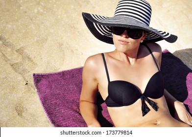 Young glamorous woman in a summer hat, sunglasses and a black bikini laying on the beach.