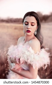 Young glamorous woman wearing feathers outdoors