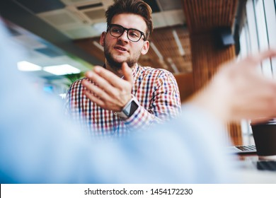 Young glassed hipster guy discussing news with friend indoors, serious Caucasian student in spectacles for provide eyes protection talking with colleague brainstorming togetherness in coffee shop