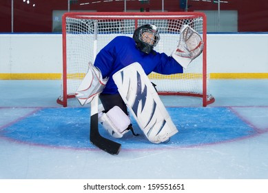 Young goalkeeper catching a  flying puck in knee position.