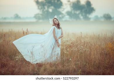 Young goddess. Morning field, foggy sunrise. Pagan spirit