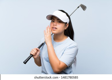 Young golfer Asian girl over isolated blue background whispering something