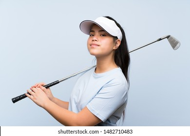 Young golfer Asian girl over isolated blue background