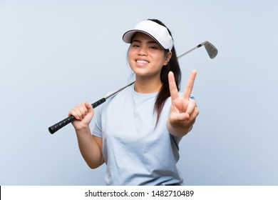Young golfer Asian girl over isolated blue background smiling and showing victory sign