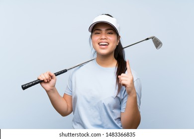 Young golfer Asian girl over isolated blue background pointing up a great idea