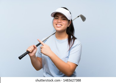 Young golfer Asian girl over isolated blue background pointing to the side to present a product