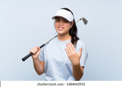 Young golfer Asian girl over isolated blue background inviting to come with hand. Happy that you came