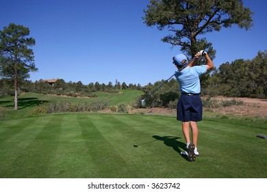 Young golfer hitting a nice tee shot with ball clearly visible