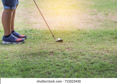Young  golfer with metal golf club preparing to drive the golf ball on the fairway