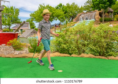 young golfer on the mini golf course. Cheerful child playing mini golf