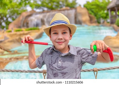 young golfer with putter and ball. the boy on the mini golf course