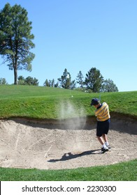 Young golfer successfully hitting golf ball out of a sand trap