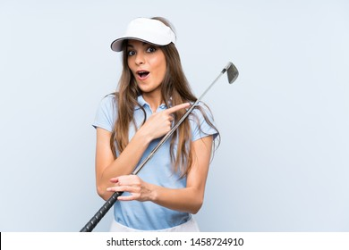 Young golfer woman over isolated blue wall surprised and pointing side