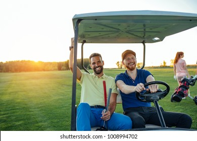 Young golfers driving in a cart on a golf course