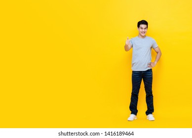 Young good looking Asian man standing with thumbs up gesture isolated on bright yellow studio background with copy space