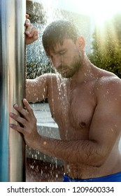 Young Good Looking And Attractive Man With Muscular Body Wet Taking Shower In Bath. handsome attractive men showering next to swimming pool. water drops are falling on his torso