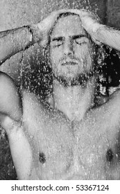 young good looking and attractive man with muscular body wet taking shower in bath with black tiles in background