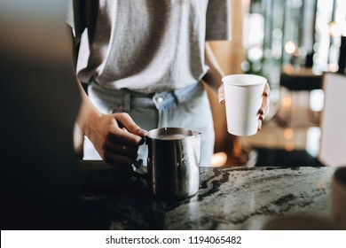 A young good looking blonde,wearing casual style,holds a glass and milk frother in a cozy coffee shop.