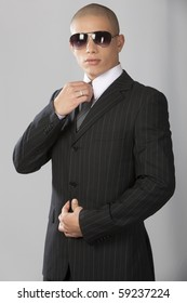 A young good looking businessman on a gray background.