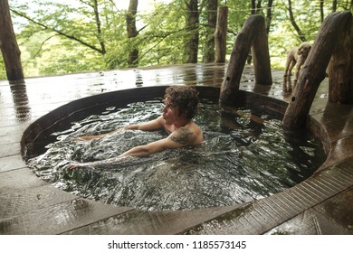 young good looking male is taking a dip in the hot tub. close up side view photo. amazing forest on the background of the photo