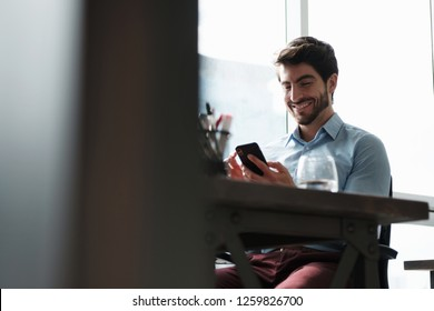A young good looking man at office smiling after sending message using his smartphone. Happy Handsome Caucasian Businessman use his phone to send text message with app. Technology usage young people