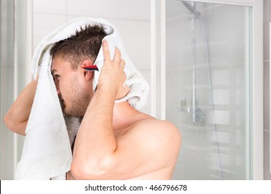 Young good-looking guy dries his wet hair with a clean towel after washing procedures in the modern tiled bathroom