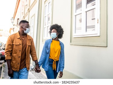 Young gorgeous african hipster couple holding hands and walking down the street during corona virus outbreak.