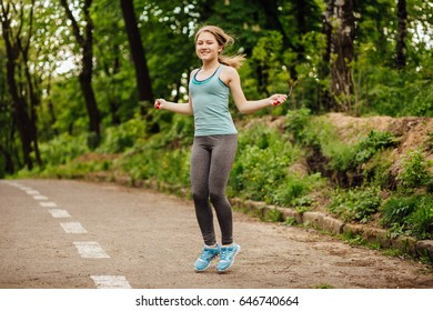 Young gorgeous blonde sporty woman in turquoise t-shirt, gray leggings and sneakers workout with skipping rope in park outdoor.