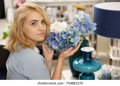 Young gorgeous blonde woman smiling to the camera over her shoulder holding beautiful hortensia flowers decorating her cozy home lifestyle lesire designer interior homeware relaxation floral