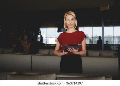 Young gorgeous businesswoman holding in hands digital tablet while standing in modern restaurant interior, successful female CEO dressed in elegant clothes posing while work on portable net-book