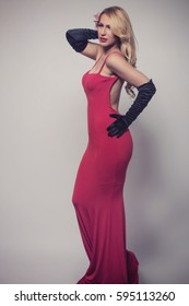 Young gorgeous Caucasian blonde in red dress. Retro look.