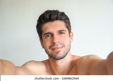Young gorgeous man with a perfect hair and skin is taking a selfie in his bathroom