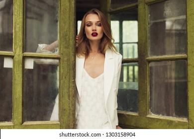 Young gorgeous pensive woman in white jacket and dress thoughtfully looking in camera leaning on beautiful old door