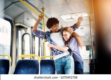 Young gorgeous playful girl is hugging her cheerful and surprised boyfriend in a bus.