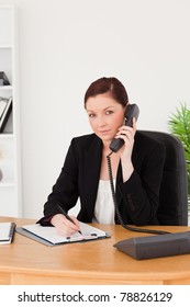 Young gorgeous red-haired woman in suit writing on a notepad and phoning while sitting in an office