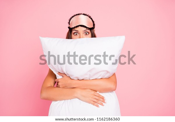Young gorgeous shocked lady wearing eye mask, hugging pillow, hiding. Isolated over pink pastel background