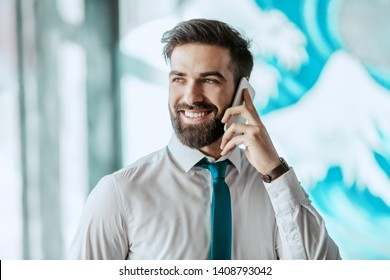 Young gorgeous smiling Caucasian businessman in formal wear talking on the phone while standing at office.