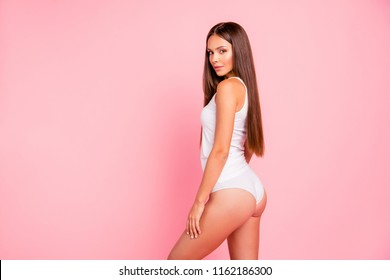 Young gorgeous straight-haired brunette smiling lady wearing sleepwear, side profile view. Isolated over pink pastel background